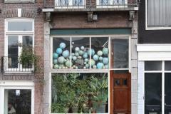 Amsterdam-167-Wereldbollen-achter-raam-bij-Blauwbrug